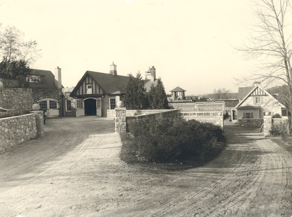 A 1917 view of Tower Garage, the second greenhouse and Twin Cottage (right). Copyright Cranbrook Archives.